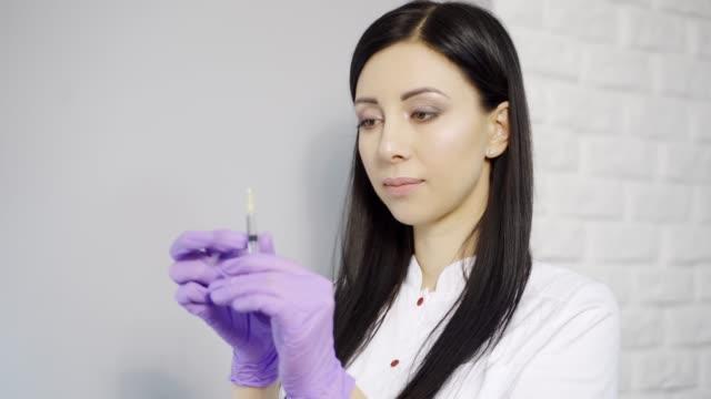 красивый косметолог с длинными волосами проверяет шприц с инъекцией перед введением препарата клиенту в салоне красоты. - white background стоковые видео и кадры b-roll