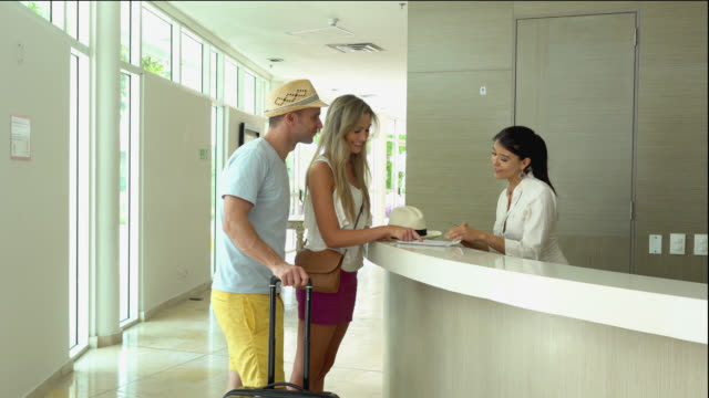 Beautiful couple checking in the hotel Beautiful couple checking in the hotel and hostess handing them the key card hotel stock videos & royalty-free footage