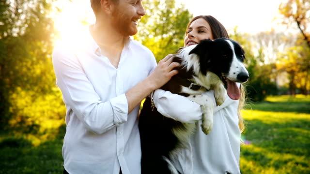 vídeos de stock e filmes b-roll de beautiful couple cuddling and walking dogs outdoors - parque público