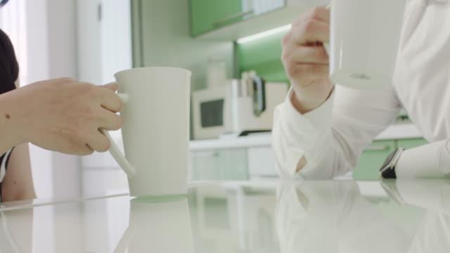 台所でコーヒーを飲んでいる美しいカップル。朝。クローズ アップ。 - マグカップ点の映像素材/bロール