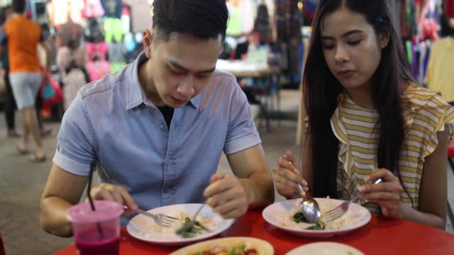 beautiful couple eating street food - sud est asiatico video stock e b–roll