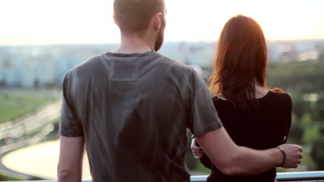 beautiful couple embrace on background of the city Beautiful young couple, man and woman, embrace on a background of the city at sunset comfort stock videos & royalty-free footage