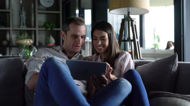 stockvideo's en b-roll-footage met mooie paar plezier thuis ontspannen op de bank kijken naar iets op tablet pc - een tablet gebruiken
