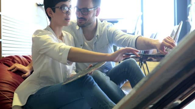 vidéos et rushes de beau couple amoureux travaillant sur le projet de classe d'art ensemble - toile à peindre