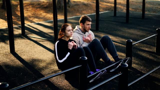 schönes paar ist sport im freien sit mit metallstangen, die sitzen auf dem boden training bauchmuskeln tun. menschen, körper und mühe konzept. - turngerät mit holm stock-videos und b-roll-filmmaterial