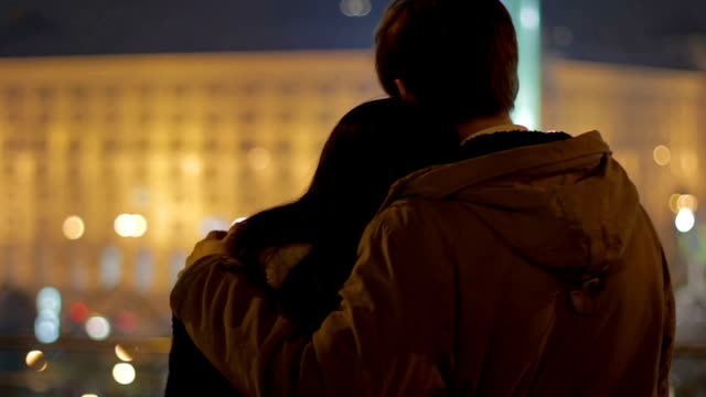 Beautiful couple lovingly hugging each other on date, enjoying night city view video
