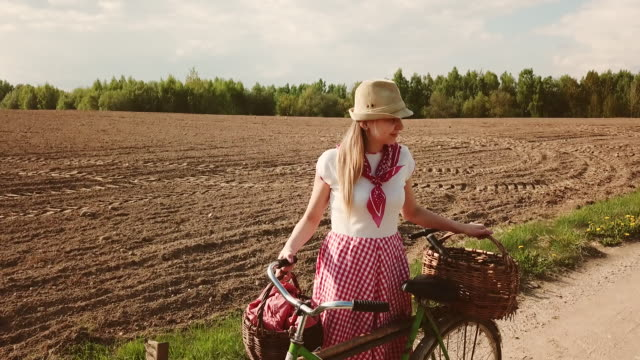 a beautiful couple of farmers is standing on the field. - cestino della bicicletta video stock e b–roll