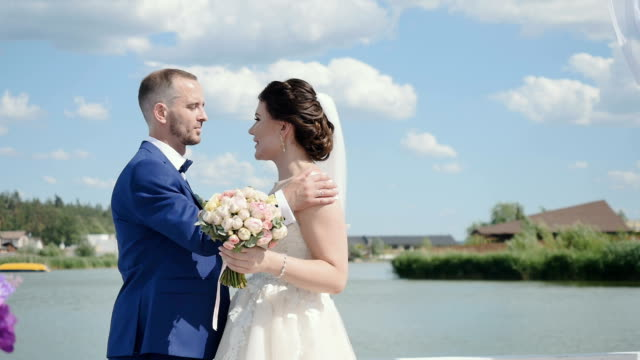 Beautiful couple of newlyweds kisses at river background video