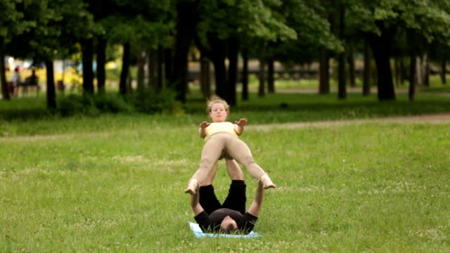 Beautiful couple practicing acro yoga. Young yoga instructors practice in a city park on green grass. Two successful young people perform acro yoga exercises. Man and a woman learn yoga at sunset. video