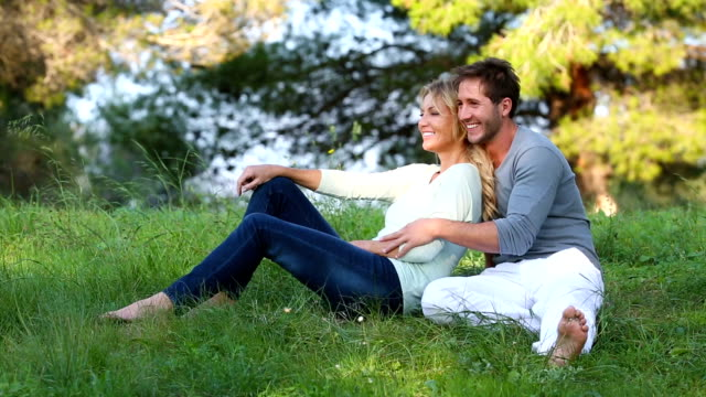 Beautiful couple sitting in the green meadow video
