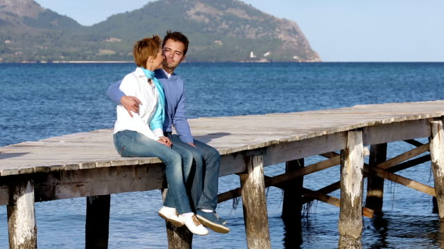 beautiful couple sitting on the jetty enjoying time together video