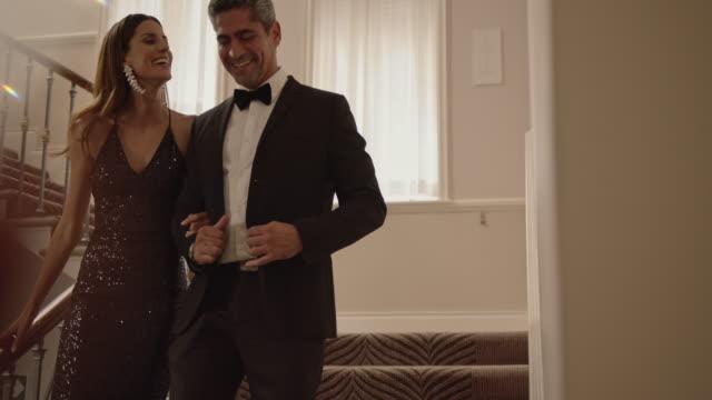 vackert par går nerför trappan - formell klädsel bildbanksvideor och videomaterial från bakom kulisserna