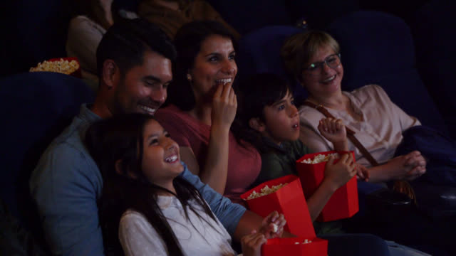 Beautiful couple with their two kids and grandmother enjoying a movie at the cinema while eating snacks Beautiful couple with their two kids and grandmother enjoying a movie at the cinema while eating snacks all smiling film industry stock videos & royalty-free footage