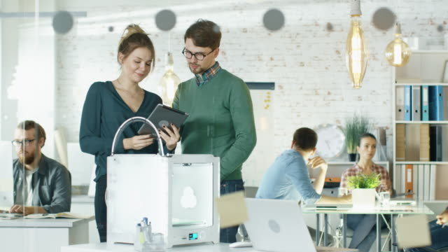 Beautiful Creative Girl Shows Tablet Computer To Her Stylish Male Colleague. They Locate in a Busy Creative Loft Office with Young People Working in Background. video