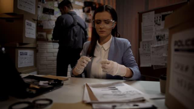 красивый криминальный эксперт, анализирующий пулю с места преступления, следствие - expert стоковые видео и кадры b-roll
