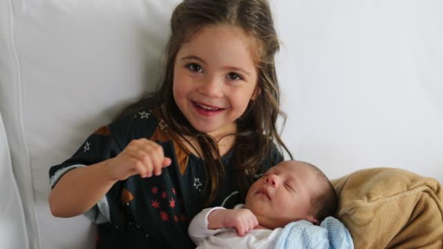 vídeos y material grabado en eventos de stock de hermosa linda familia momento hermana besando hermanito recién nacido2 - hermana