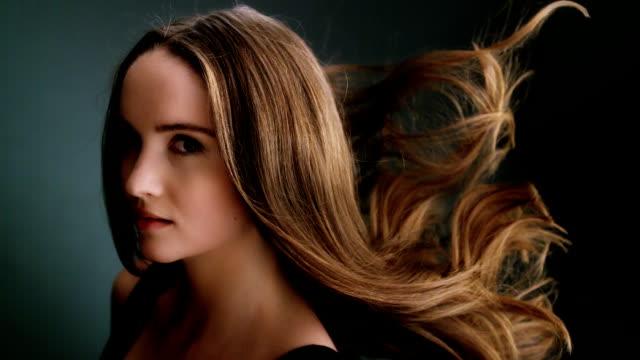 Beautiful dark blond woman tossing long hair video