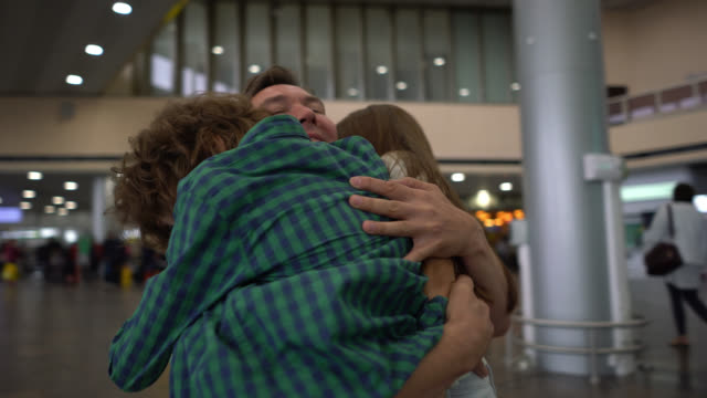 vídeos de stock e filmes b-roll de beautiful daughter and son greeting their dad with excitement at the airport hugging him - abraçar