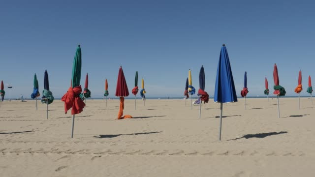 Beautiful day at Deauville city in Normady 4K 2160p 30fps UltraHD footage - Parasol sun protection at the beach in France slow pan 3840X2160 UHD video Beautiful day at Deauville city in Normady 4K 2160p 30fps UltraHD footage - Parasol sun protection at the beach in France slow pan 3840X2160 UHD video normandy stock videos & royalty-free footage