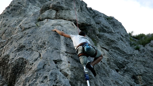 Beautiful day for free climbing One man, disability young man with prosthetic leg, free climbing on a rocky mountain in nature. amputee stock videos & royalty-free footage