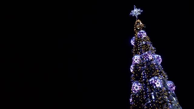 夜空の背景に美しい装飾クリスマスツリー。新年とクリスマスのコンセプト、コピースペース、ぼやけた - 十二月点の映像素材/bロール