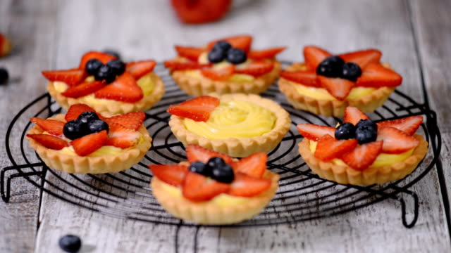 beautiful delicious summer tartlets with fresh custard creamy filling topped with strawberry and blueberry - decorazione per dolci video stock e b–roll