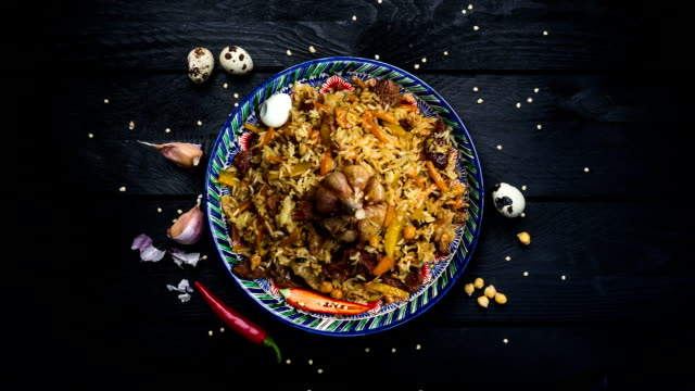 Beautiful dish with pilaf and oriental ornament rotates on a black wooden background. Top view video