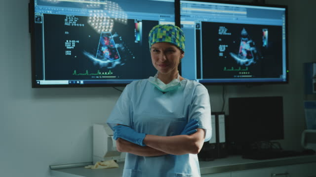 Beautiful doctor with arms crossed against results Handheld shot of confident female surgeon standing against ultrasound scan. Portrait of beautiful doctor is with arms crossed in emergency room. She is wearing scrubs at hospital. radiologist stock videos & royalty-free footage