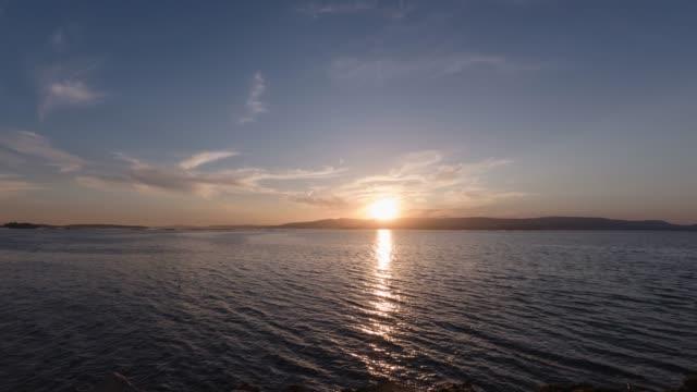 beautiful dramatic sunset over the mountains in the atlantic ocean in cloudy weather - krajobraz morski filmów i materiałów b-roll