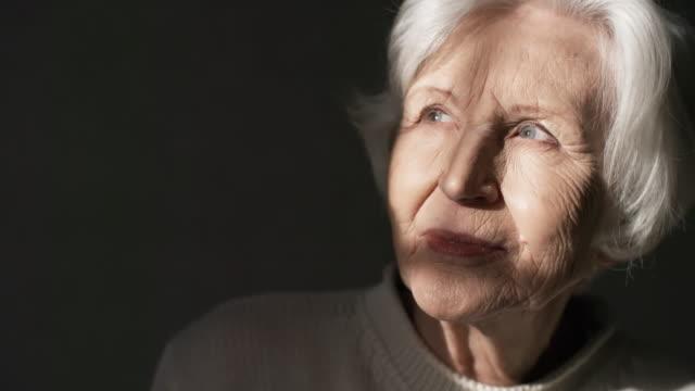 Bидео Beautiful Dreamy Elderly Lady's Face Illuminated by Sunlight