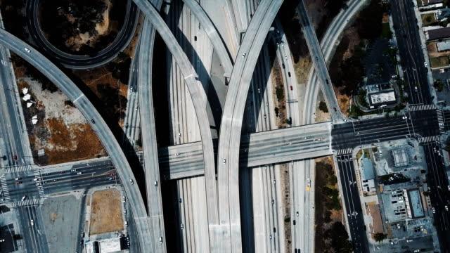 vídeos y material grabado en eventos de stock de paso elevado de drone hermosa arriba grande carretera empalme intercambio con estructura compleja de múltiples caminos y pasos elevados. - los angeles