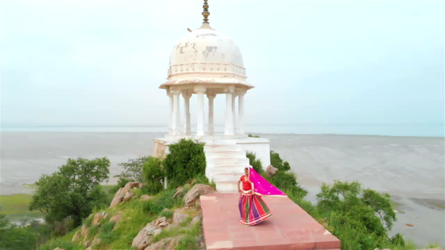 A beautiful drone shot of a elegant Indian dancer in traditional attire performing on hilltop A beautiful drone shot of a elegant Indian dancer in traditional attire performing on hilltop in the morning just before sunrise. An aerial shot of an attractive woman performing in colorful cloths sari stock videos & royalty-free footage