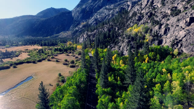 Beautiful drone shot on a lonesome road in the California mountains as the trees are changing colors. video