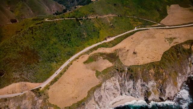 vídeos de stock e filmes b-roll de beautiful drone top view of cars on amazing highway 1 near pacific ocean sunny landscape panorama in big sur california. - estrada 001