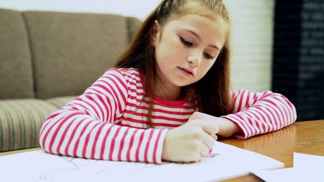 bella bambina di otto anni rilassante e facendo un po 'di colorazione nel soggiorno - 8 9 anni video stock e b–roll