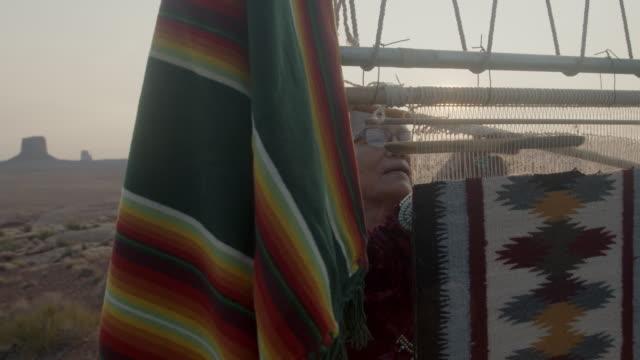 bella anziana nativa americana navajo donna nel vasto monument valley tribal park nel deserto dell'arizona facendo una tradizionale coperta indiana usando un telaio vecchio stile - artigianato video stock e b–roll