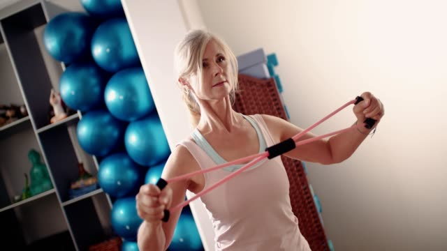beautiful elderly woman doing a stretching exercise at the gym - balance video stock e b–roll
