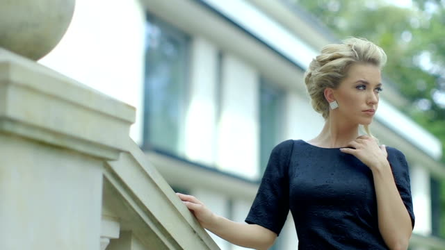 Beautiful elegant woman in a black dress walking up the stairs, outdoors. video