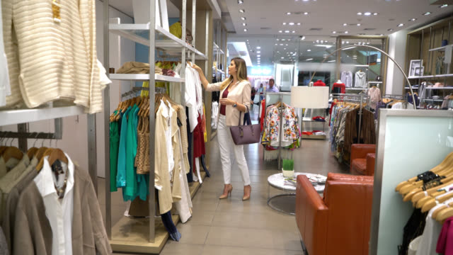 Beautiful elegant women looking at clothes from different racks at a women's store