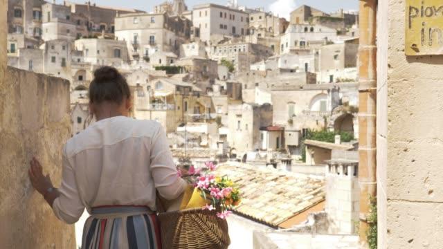 vídeos de stock, filmes e b-roll de elegante jovem bonita andando em matera itália em um ponto de vista do alto da varanda com paisagem. vestido com chapéu e saia de moda. - característica arquitetônica