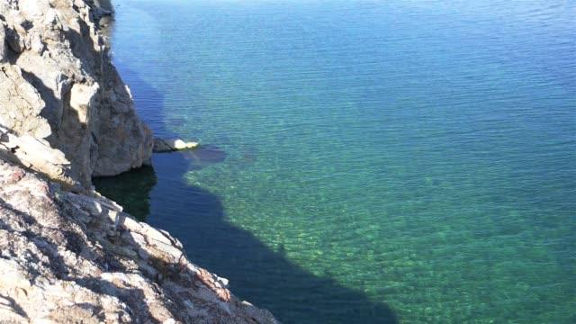 vídeos de stock e filmes b-roll de beautiful emerald water wave and rock cliff of baikal lake in olkhon island, irtkutsk russia - lago baikal