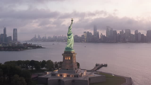 Beautiful Establishing Shot of Statue of Liberty looking towards Manhattan Scenic Skyscraper Skyline covered in Fog in early morning or Sunset, Aerial Orbit Drone Shot