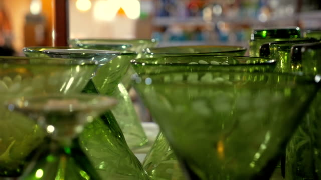 Beautiful etched green cocktail glasses and goblets on a shelf - dolly CU video