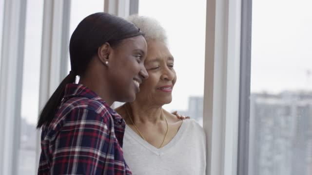 Beautiful Ethnic Mother And Daughter Smiling Together A black senior woman is with her adult daughter and they are hugging. Both women are smiling with gratitude for being able to spend time with one another. mammogram stock videos & royalty-free footage