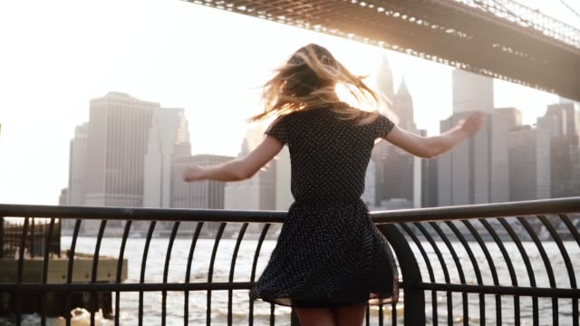 Beautiful excited traveler girl spinning on river embankment at Brooklyn Bridge with arms raised in the air slow motion Beautiful excited traveler girl spinning on river embankment at Brooklyn Bridge with arms raised in the air slow motion. Young tourist woman with flying hair enjoying best life moments of happiness. dress stock videos & royalty-free footage