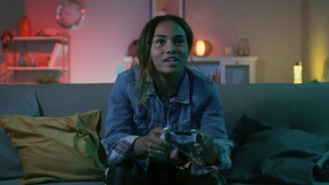 schöne begeistert junge schwarze gamer mädchen auf einer couch sitzen und spielen von videospielen auf einer konsole. sie spielt mit einem wireless-controller. gemütliche zimmer ist lit mit warmen und neonlicht. - computerspieler stock-videos und b-roll-filmmaterial