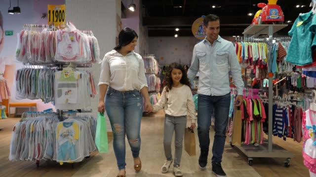 stockvideo's en b-roll-footage met prachtige familie op een thrift kinderen slaan kleren praten en wijzen terwijl de handen kijken - discountwinkel