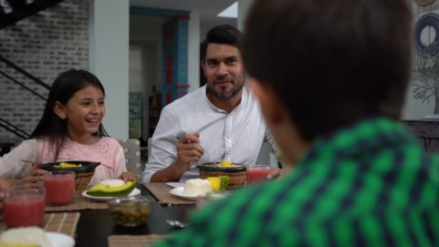 Beautiful family at home enjoying a delicious ajiaco for lunch while talking
