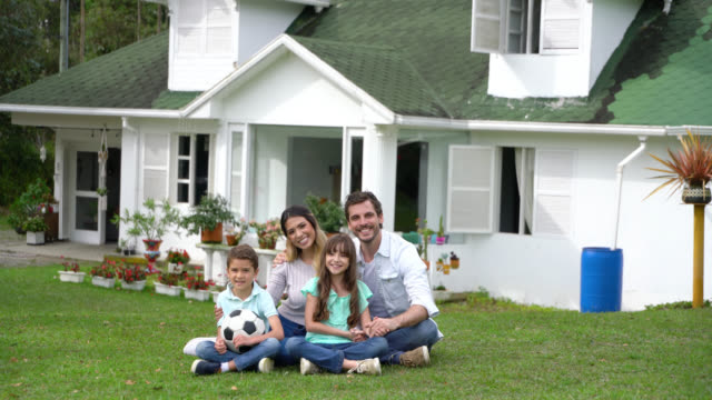 stockvideo's en b-roll-footage met mooie familie in hun achtertuin zittend op het gras glimlachend op camera erg blij - garden house