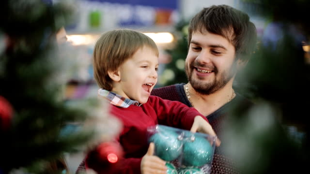 Beautiful family is shopping for Christmas at the supermarket. Mum takes son Christmas balls and boy smiling. video